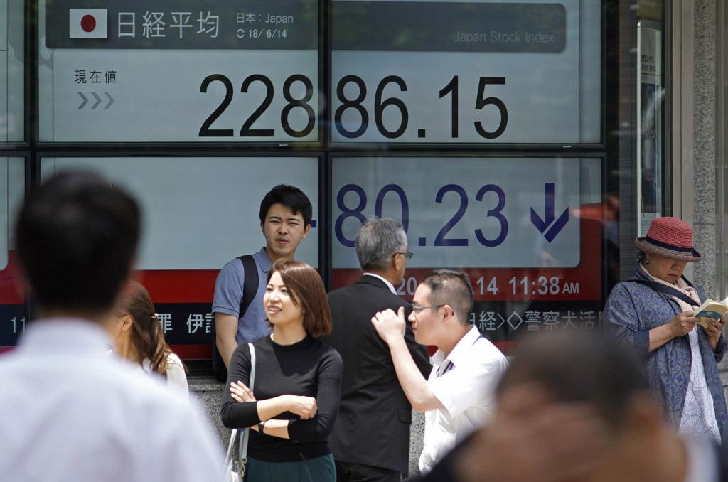 People walk by an electronic stock board of a securities firm in Tokyo, Thursday, June 14, 2018. Asian stock markets slumped on Thursday with South Ko...