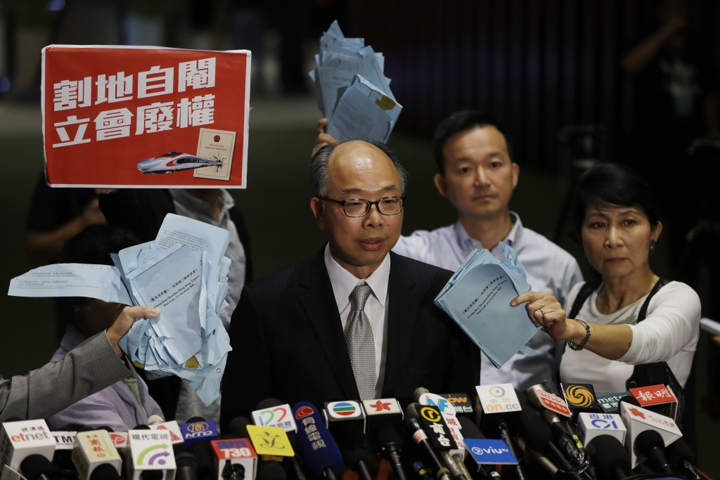 Hong Kong Secretary for Transport and Housing Frank Chan Fan, center, speaks to the media surrounded by pro-democracy lawmakers after a controversial