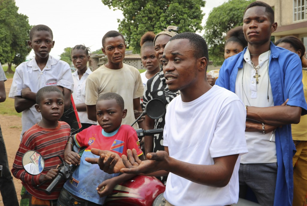 In this photo taken Thursday, May 31, 2018, motorcycle taxi driver Jean Cedric speaks of his fears outside Wangata hospital in the town of Mbandaka, C