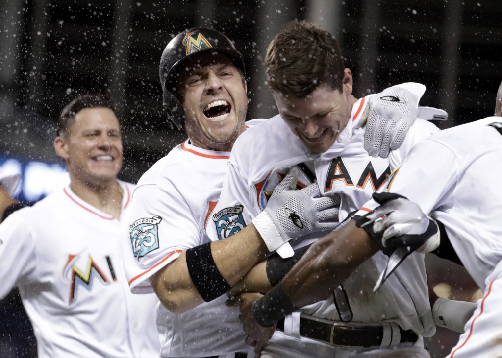 Miami Marlins' J.B. Shuck, center, celebrates with Brian Anderson, right, after Anderson hit a sacrifice fly to score Miguel Rojas during the ninth in