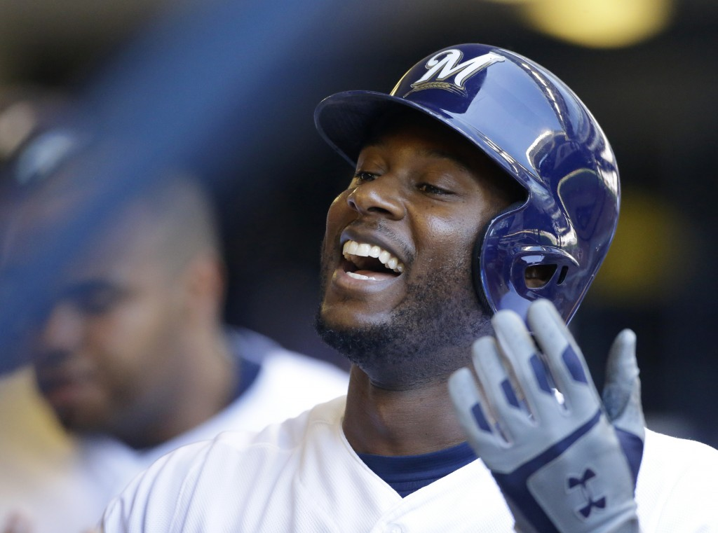 Milwaukee Brewers' Lorenzo Cain celebrates in the dugout after hitting a solo home run in the third inning of a baseball game against the Chicago Cubs