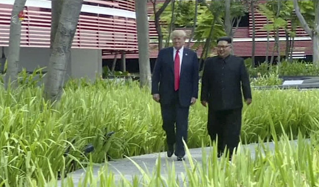 In this image made from video released by KRT on June 14, 2018, shows North Korean leader Kim Jong Un, right, taking a walk through the a garden with