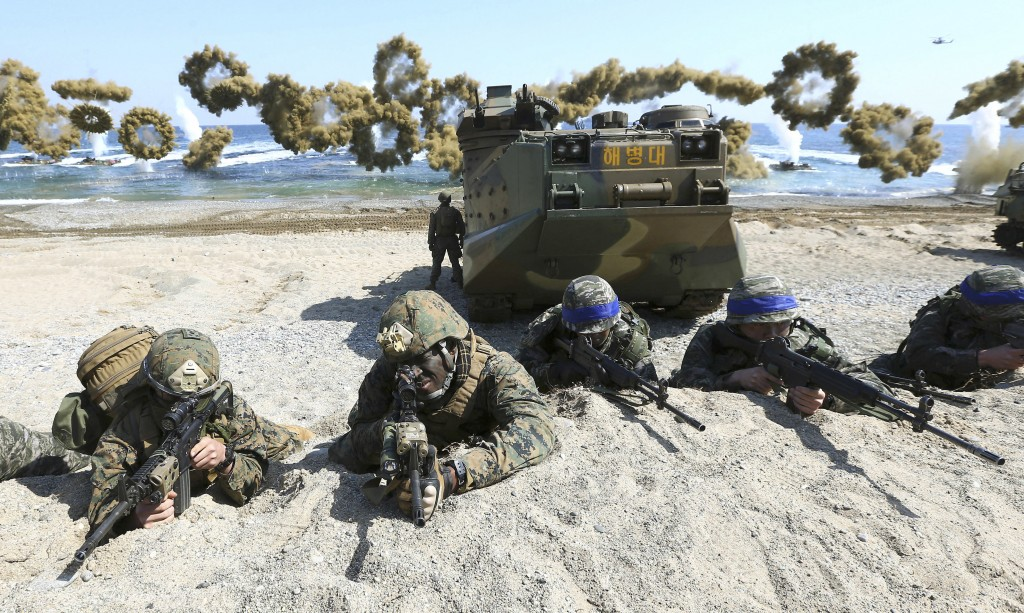 FILE - In this March 12, 2016, file photo, Marines of the U.S., left, and South Korea wearing blue headbands on their helmets, take positions after la