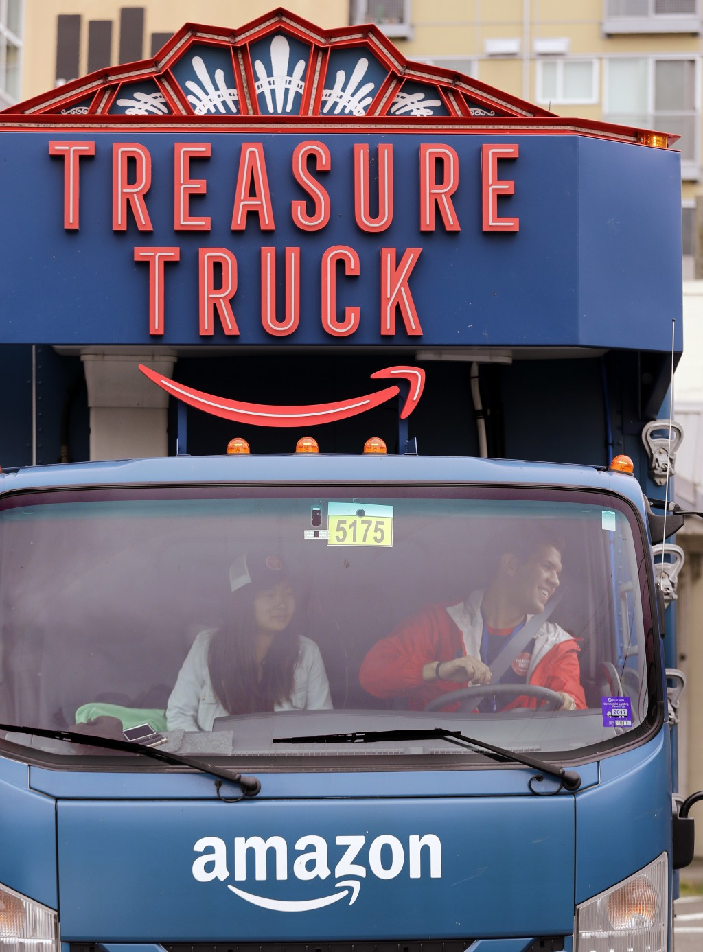 In this May 24, 2018, photo Amazon worker Tony Biallas, right, backs-up an Amazon Treasure Truck into a parking spot as intern Mavis Rong rides shotgu