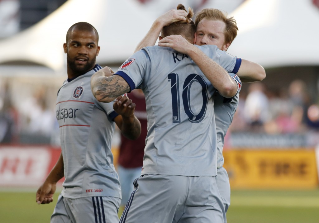 Chicago Fire forward Aleksandar Katai, center, is hugged by midfielder Dax McCarty, right, as defender Kevin Ellis looks over at them after Katai's go