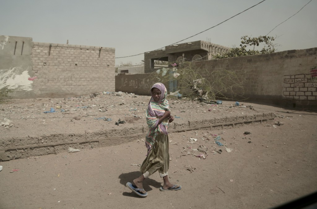 In this Feb. 12, 2018, photo, a girl walks alone on a street in al-Khoukha, Yemen. Since the Saudi-led coalition began its bombing campaign against th