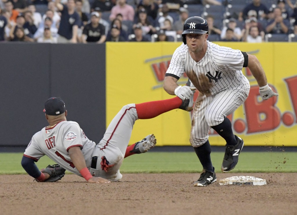 New York Yankees' Brett Gardner, right, heads to third after stealing second base as Washington Nationals shortstop Wilmer Difo (1) couldn't handle th