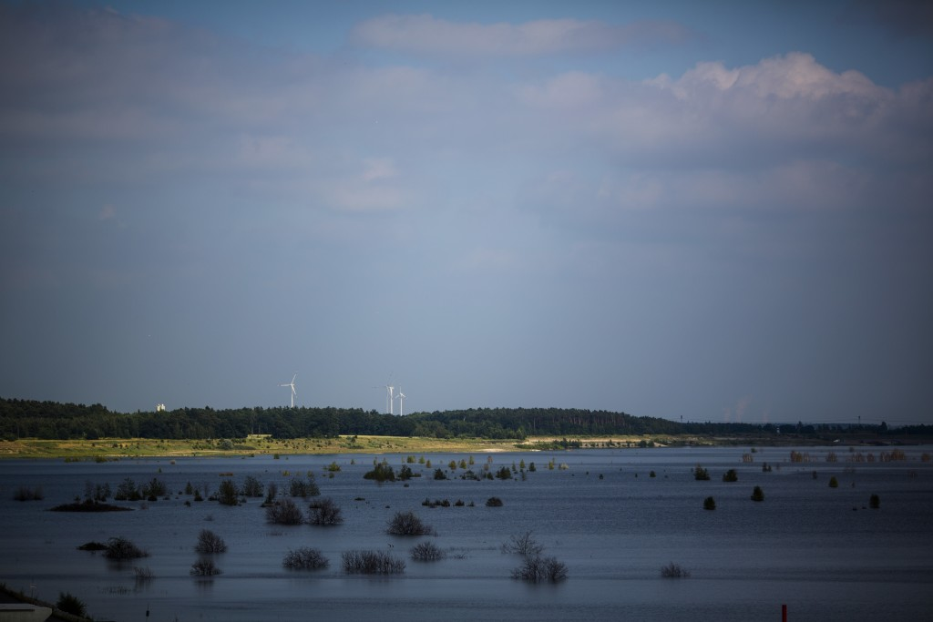 In this Tuesday, June 5, 2018 photo, trees rise out of the lake Grossraeschen See, a flooded lignite coal pit, in the Lusatia (Lausitz) area near the
