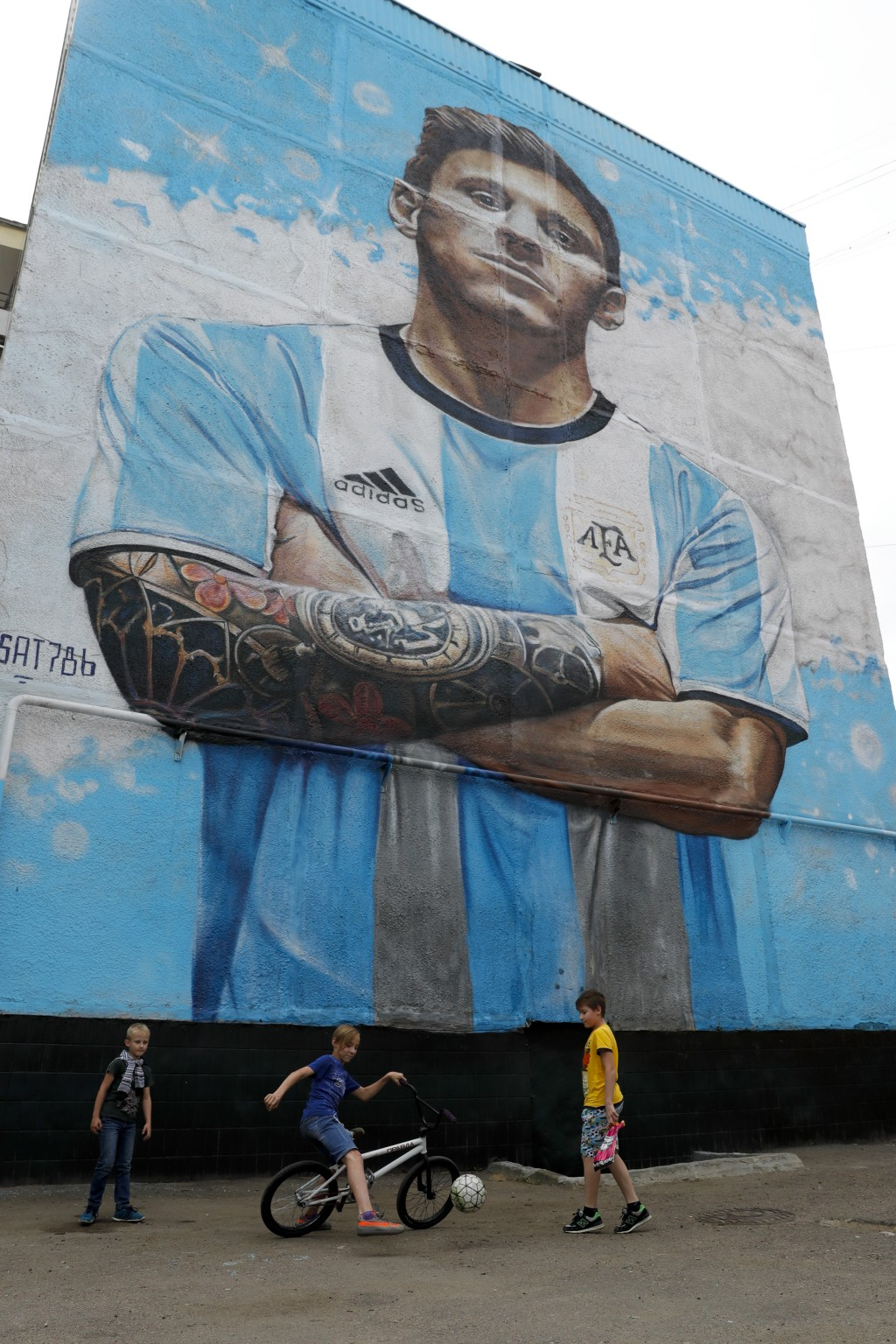 Boys play ball under a mural of Argentina's soccer star Lionel Messi during the 2018 soccer World Cup in Bronnitsy, Russia, Thursday, June 14, 2018. (