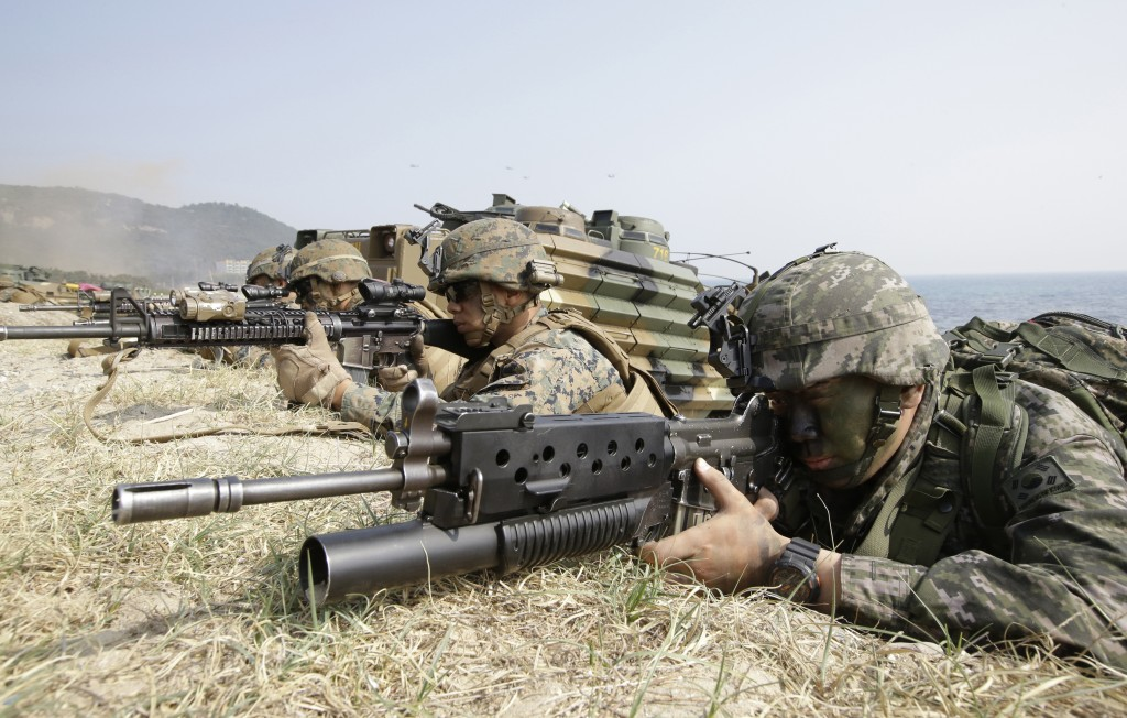 FILE - In this March 30, 2015, file photo, marines of South Korea, right, and the U.S aim their weapons near amphibious assault vehicles during U.S.-S