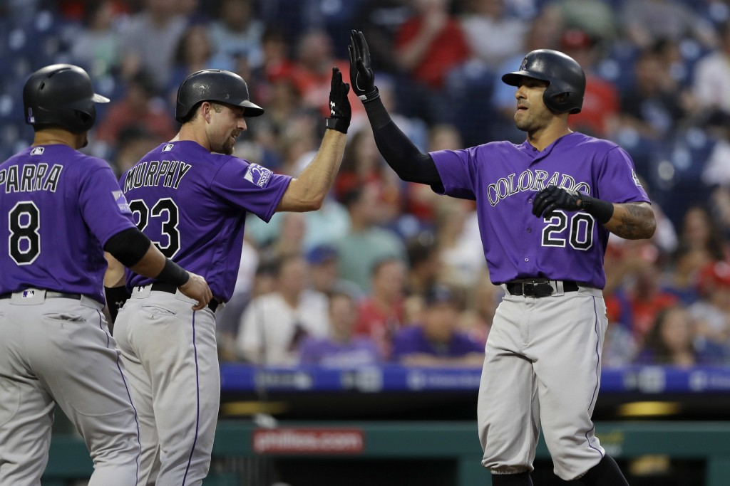 Colorado Rockies' Ian Desmond (20) celebrates with Tom Murphy (23) and Gerardo Parra (8) after Desmond's two-run home run off Philadelphia Phillies st