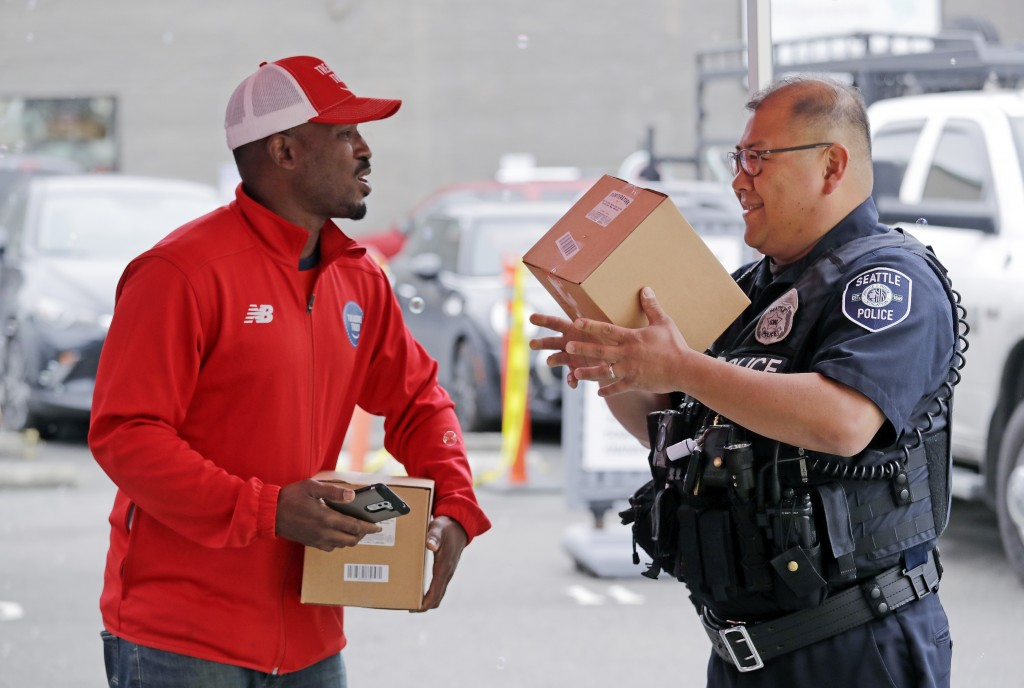 In this May 24, 2018, photo Amazon worker Khayyam Kain, left, hands off a package to Seattle police officer Pablo Lee at an Amazon Treasure Truck in S