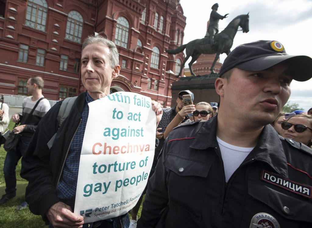 "Russian police detain Gay rights activist Peter Tatchell, center, as he holds a banner that read ""Putin fails to act against Chechnya torture of gay p"