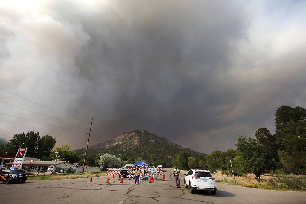 Smoke rises from the 416 Fire behind the U.S. Highway 550 road block at Cometti Lane on Wednesday, June 13, 2018, near Durango, Colo. (Jerry McBride/T