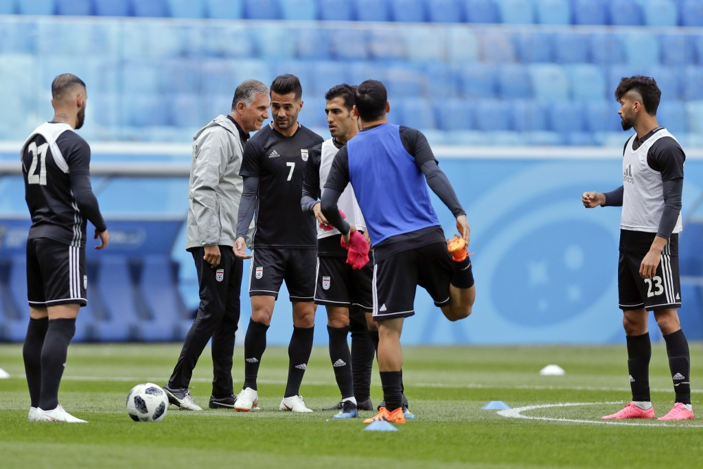 Iran head coach Carlos Queiroz walks among his player during the official training of Iran on the eve of the group B match between Morocco and Iran at