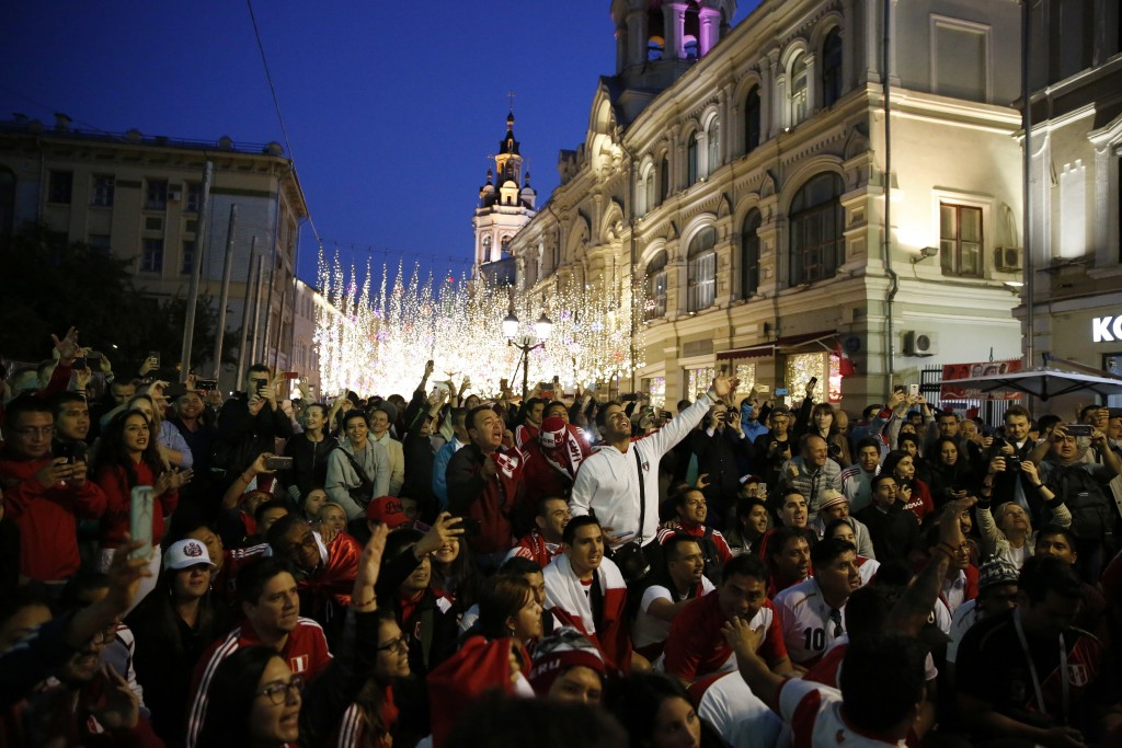 Peru soccer fans squat during a chant, as fans from participating countries gathered to celebrate and cheer on their teams on the eve of the 2018 socc