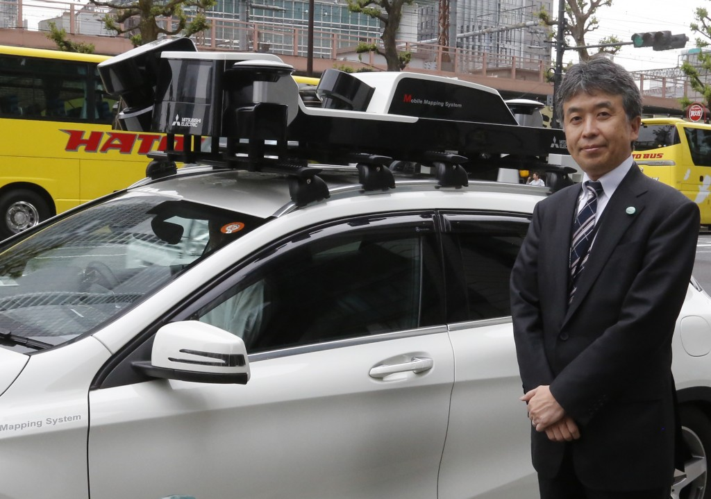 In this May 31, 2018, photo, Mitsubishi Electric Corp. Senior General Manager Yasuhide Shibata, who oversees the mapping project, stands next to a car