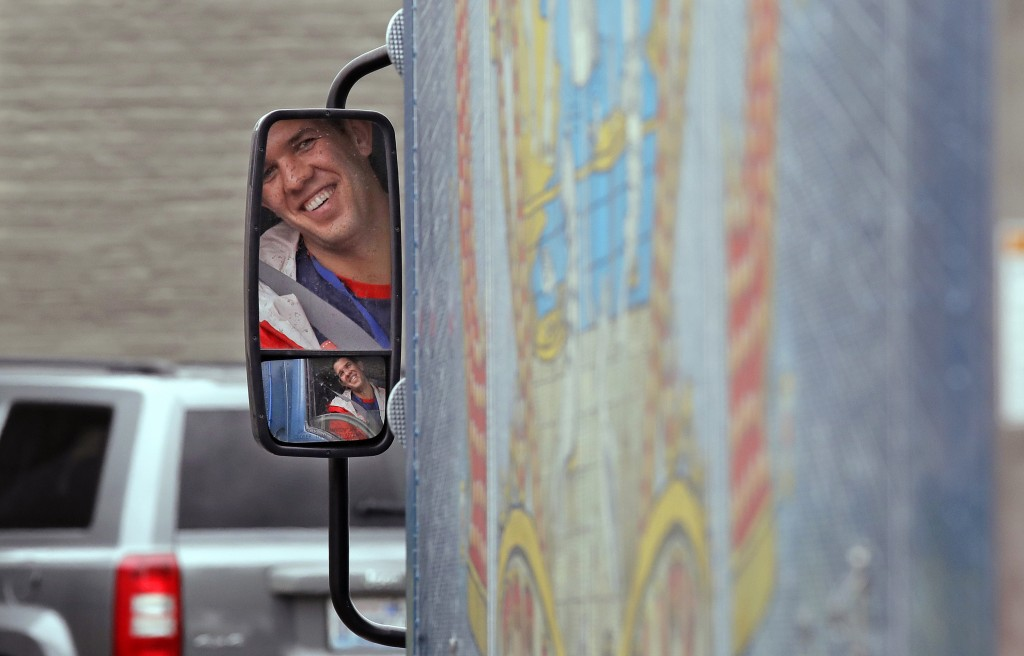In this May 24, 2018, photo Amazon worker Tony Biallas looks through a mirror as he backs up an Amazon Treasure Truck into a parking spot in Seattle.