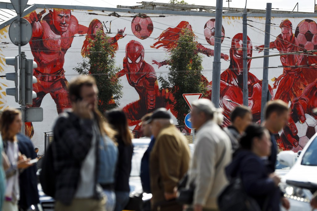 People cross the road passing by the graffiti of the Marvel Universe fictional characters playing with soccer balls in the background in Moscow, Russi