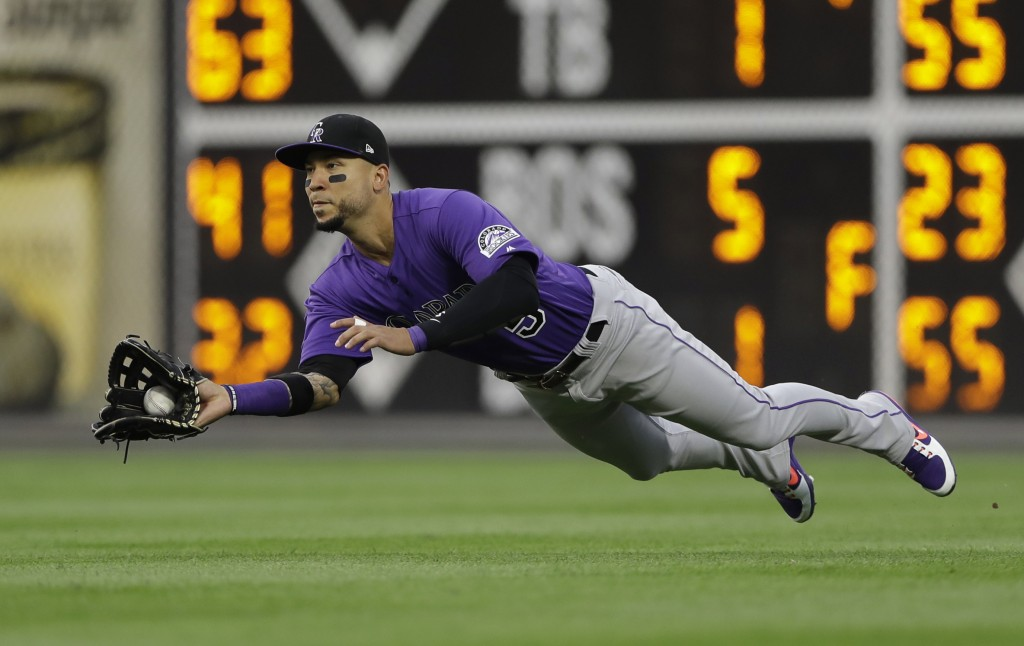 Colorado Rockies right fielder Carlos Gonzalez dives for and catches a fly ball hit by Philadelphia Phillies' Jorge Alfaro during the third inning of