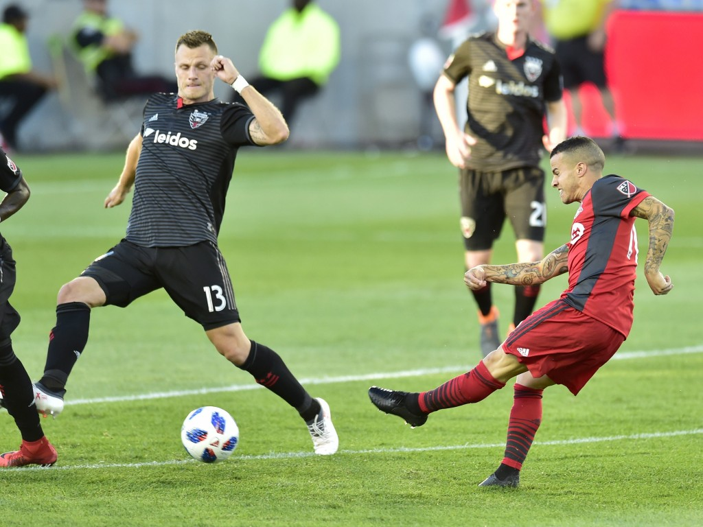 Toronto FC forward Sebastian Giovinco (10) take a shot toward the net as D.C. United's Frederic Brillant (13) defends during the first half of an MLS