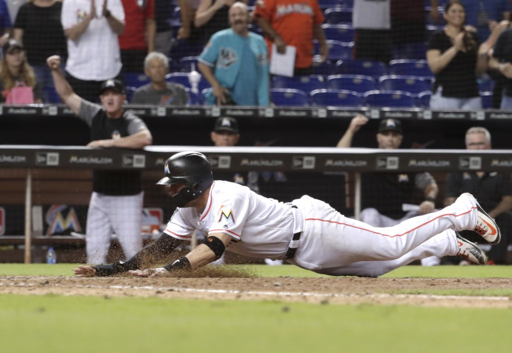 Miami Marlins' Miguel Rojas scores the game-winning run on a sacrifice fly by Brian Anderson during the ninth inning of a baseball game against the Sa