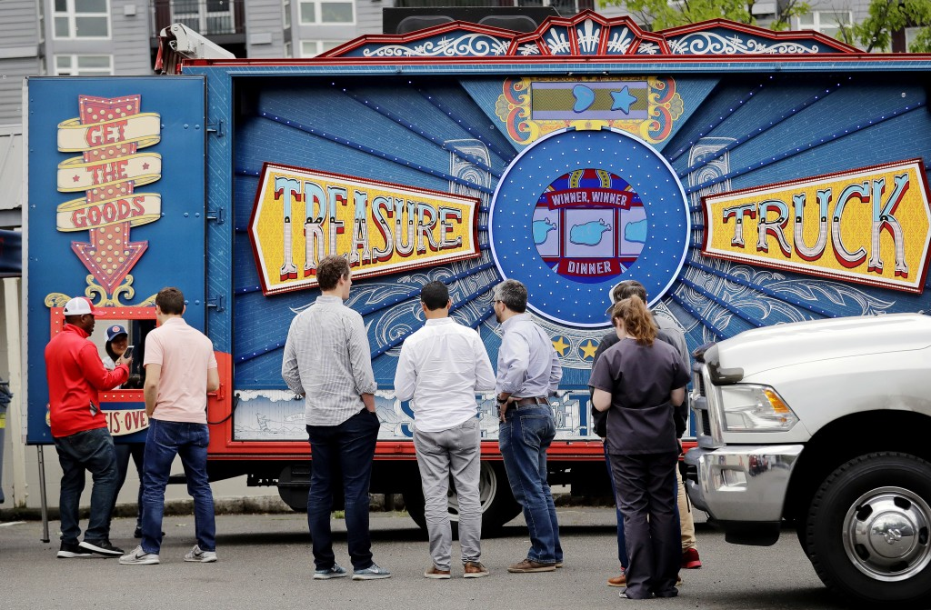 In this May 24, 2018, photo customers line-up to pick-up their deal of the day purchase at an Amazon Treasure Truck at a parking lot in Seattle. The T