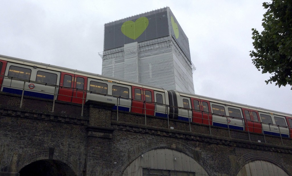 An underground tube train passes Grenfell Tower in London, Thursday, June 14, 2018. A year ago, London's Grenfell Tower high-rise was destroyed by a f