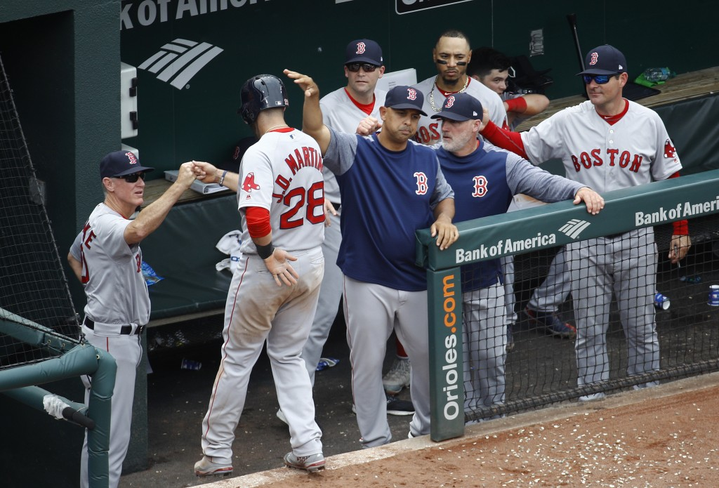 Boston Red Sox's J.D. Martinez (28) fist-bumps coaches and teammates after scoring on Eduardo Nunez's single in the fifth inning of a baseball game ag