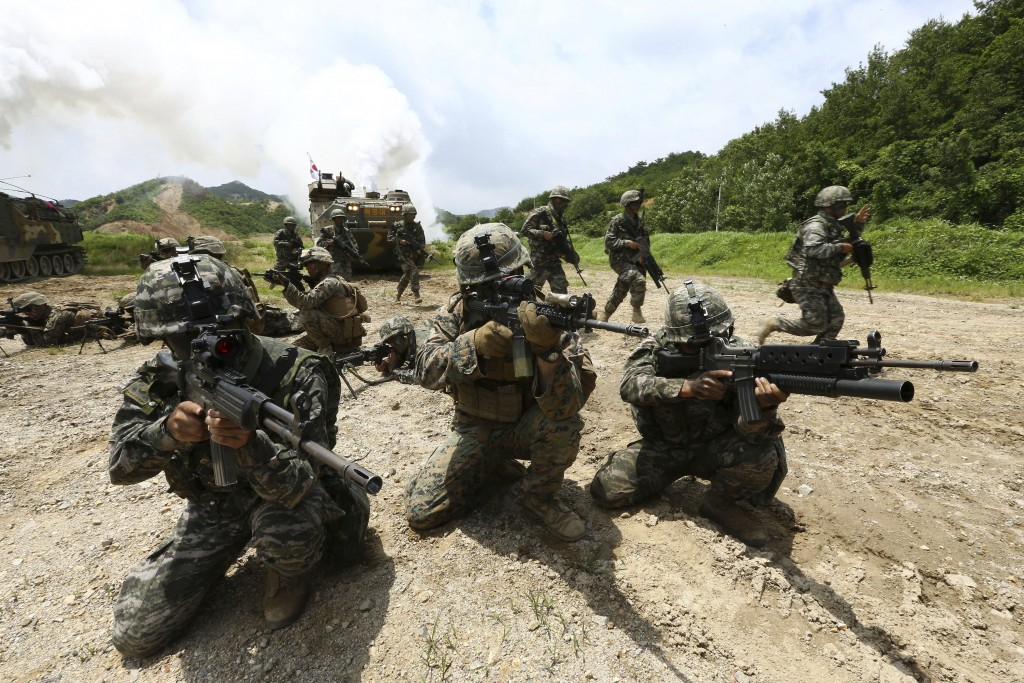 FILE - In this July 6, 2016, file photo, South Korean and U.S. marines aim their machine guns during a joint military exercise between the two countri