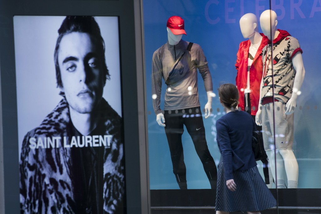 FILE- In this June 6, 2018, photo, an advertisement for Saint Laurent is seen on a bus stop display as a pedestrian walks past a window display at the