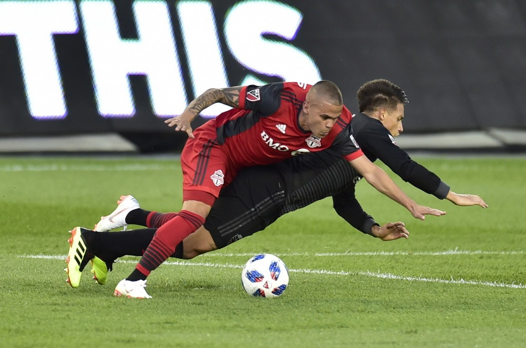 Toronto FC defender Auro, left, takes down D.C. United midfielder Yamil Asad and picks up a yellow card on the play during the first half of an MLS so