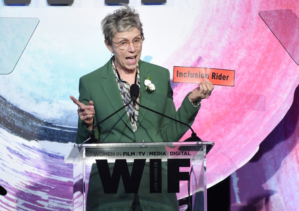 Frances McDormand, holding a sign that says Inclusion Rider, introduces Stacey L. Smith at the Women In Film Crystal and Lucy Awards at the Beverly Hi