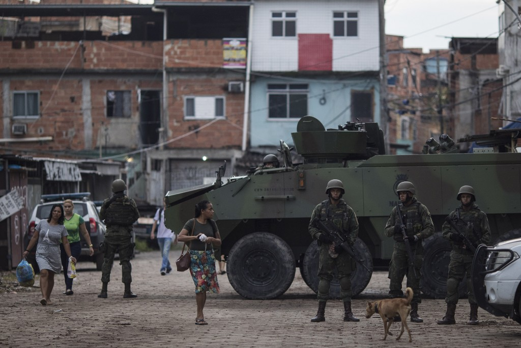 File - In this Feb.20, 2018 file photo, Brazilian marines stand in guard next to an armored vehicle a during surprise operation in Kelson's slum in Ri