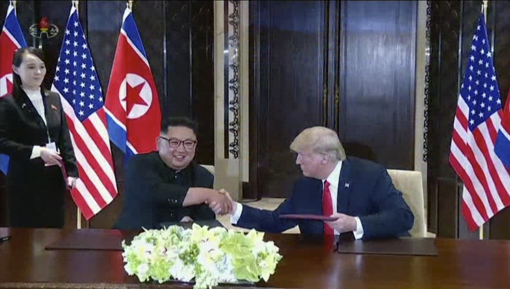 In this image made from video released by KRT on June 14, 2018, shows North Korean leader Kim Jong Un smiling at the media as he shakes hands with U.S