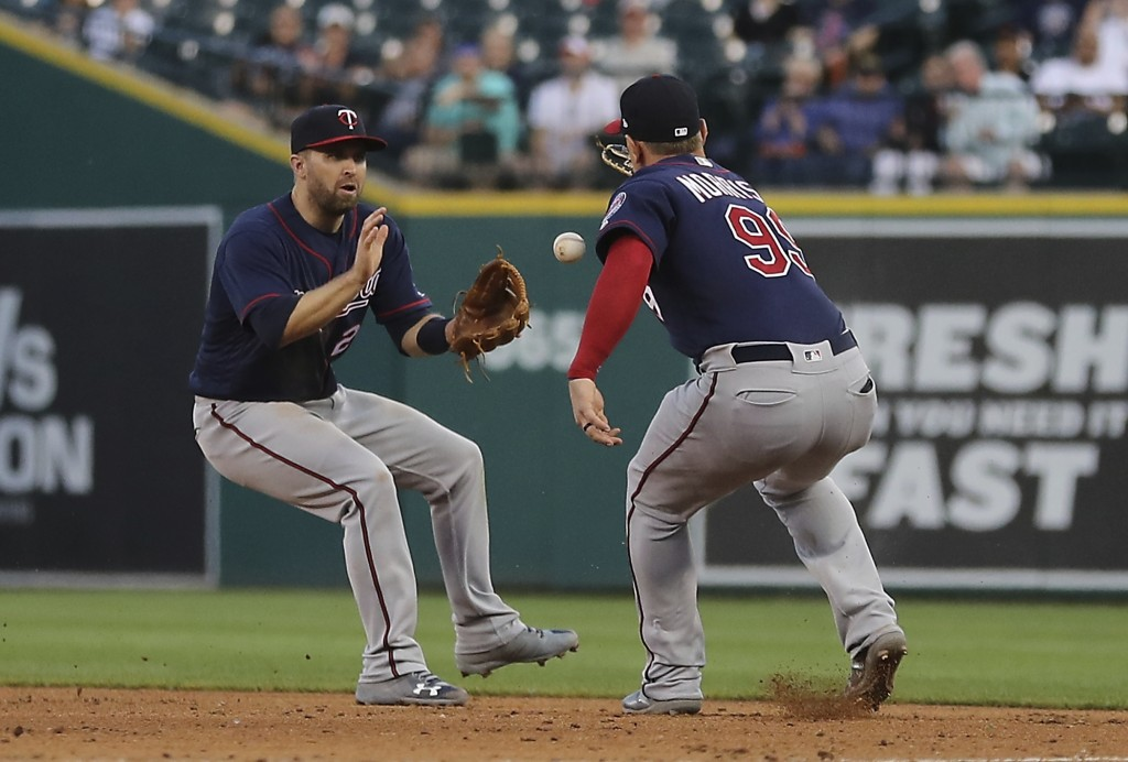 A single hit by Detroit Tigers' Leonys Martin falls between Minnesota Twins second baseman Brian Dozier, left, and first baseman Logan Morrison (99) d