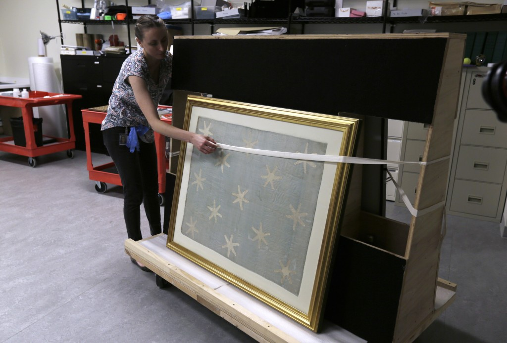 Collections manager Michelle Moskal secures the Commander-in-Chief's Standard, Wednesday, June 13, 2018, before moving it to an exhibition gallery at