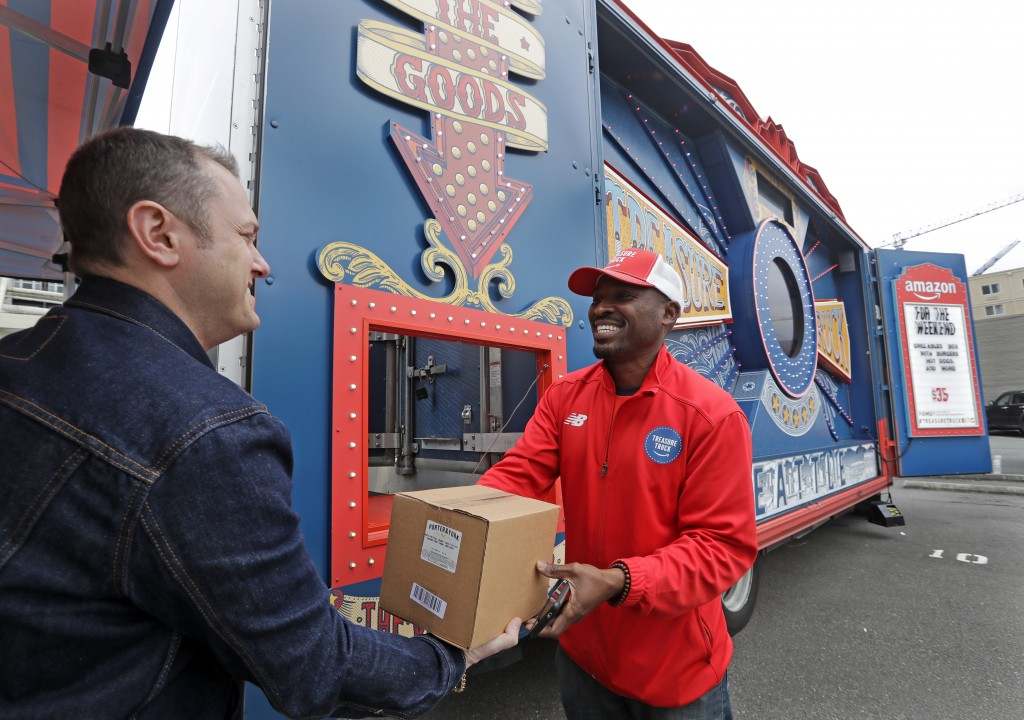 In this May 24, 2018, photo Amazon worker Khayyam Kain, right, hands off a package to a customer at an Amazon Treasure Truck in Seattle. The Treasure