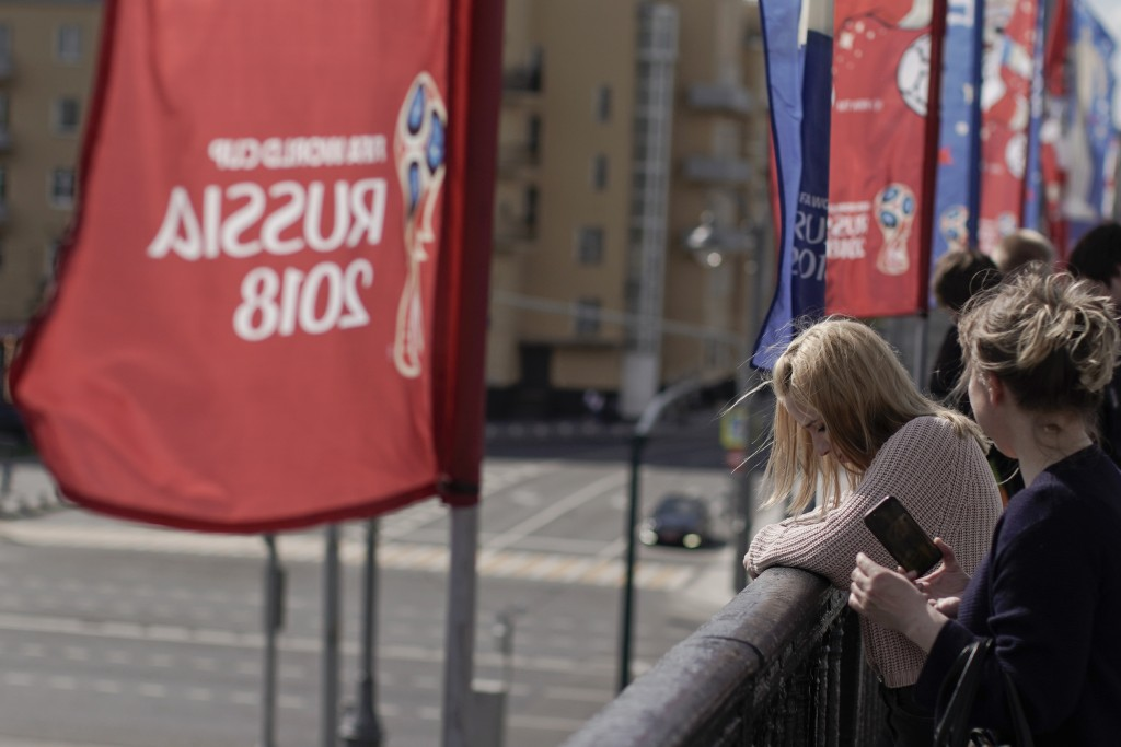 Women look over from the Krymsky Bridge, adorned with banners of the 2018 soccer World Cup, in Moscow, Russia, Wednesday, June 13, 2018. A senior Russ