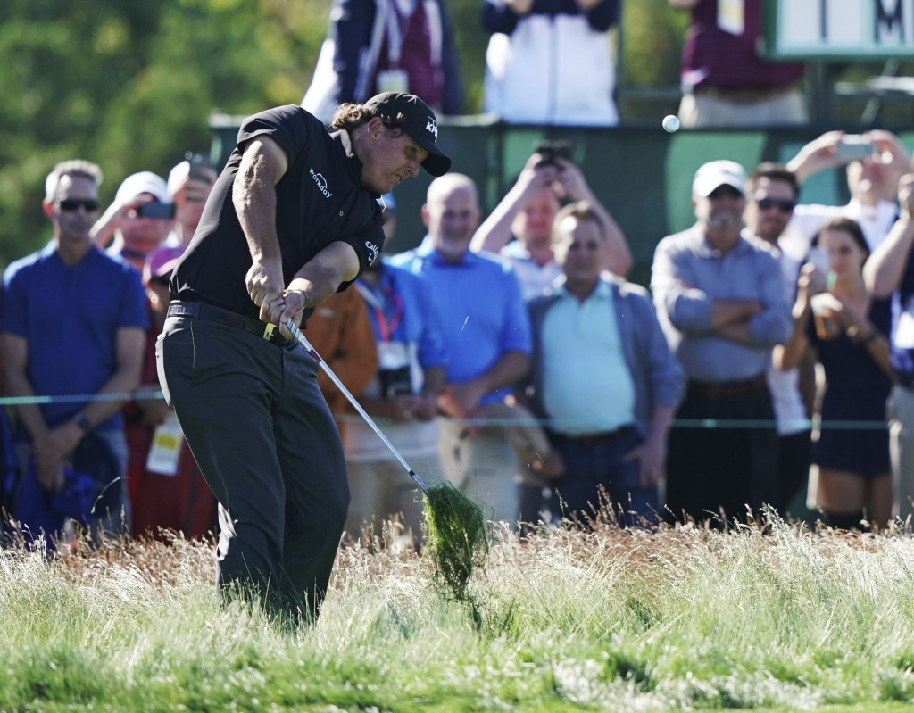 Phil Mickelson hits out of the fescue on the 12th hole during the first round of the U.S. Open Golf Championship, Thursday, June 14, 2018, in Southamp