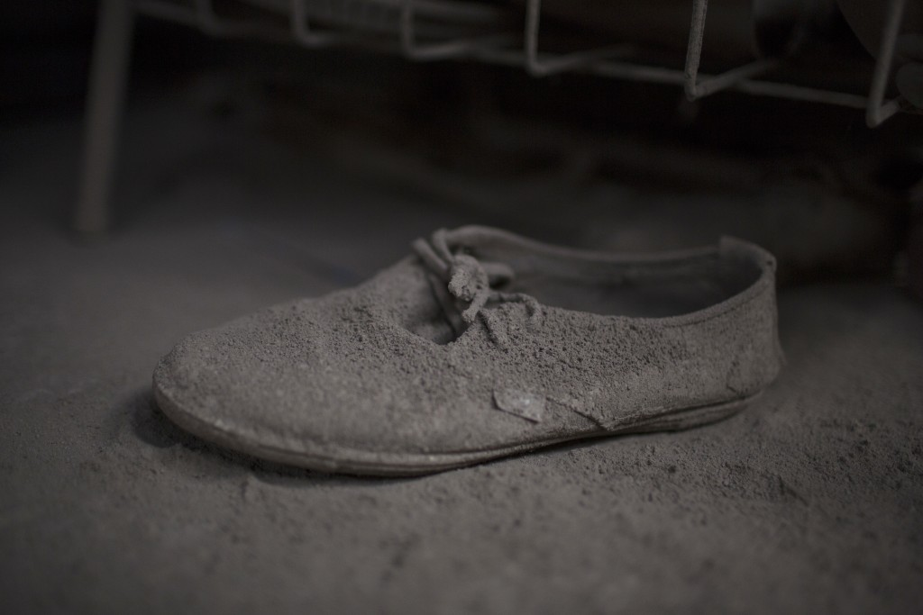 This June 9, 2018 photo shows a shoe caked in volcanic ash spewed by the Volcan de Fuego or Volcano of Fire, inside a home in San Miguel Los Lotes, Gu