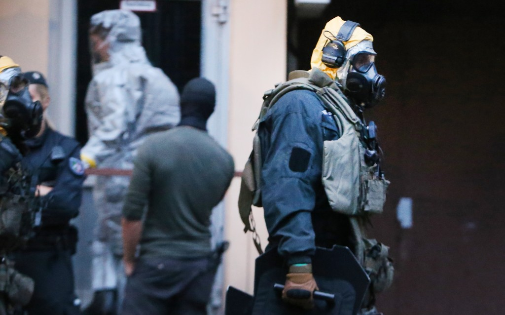 In this Tuesday June 12, 2018 photo, German police officers in protective gear leave an apartment building during an operation in Cologne, Germany. Ge