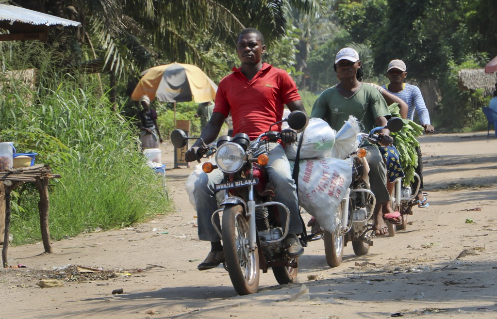 In this photo taken Saturday, June 2, 2018, motorcycle taxis drive on a street in Mbandaka, Congo. Hundreds are being vaccinated in Congo's deadly Ebo