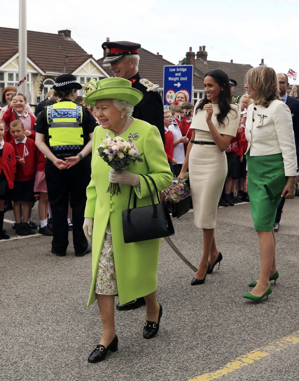 Britain's Queen Elizabeth II and Meghan, the Duchess of Sussex, second right, are welcomed by well-wishers after arriving by Royal Train at Runcorn St