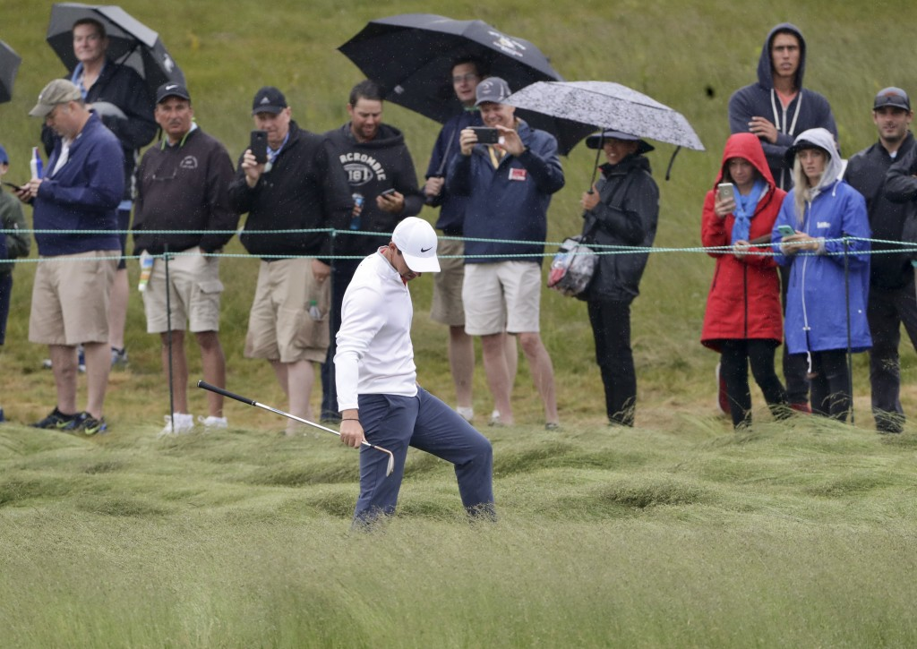 Rory McIlroy, of Northern Ireland, checks his lie in the fescue during a practice round for the U.S. Open Golf Championship, Wednesday, June 13, 2018,