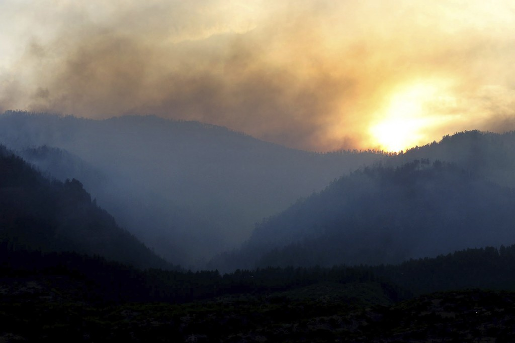 As the sun sets, smoke rises from a 416 Fire burn area west of the Falls creek Ranch subdivision late Wednesday, June 13, 2018, near Durango, Colo. (J