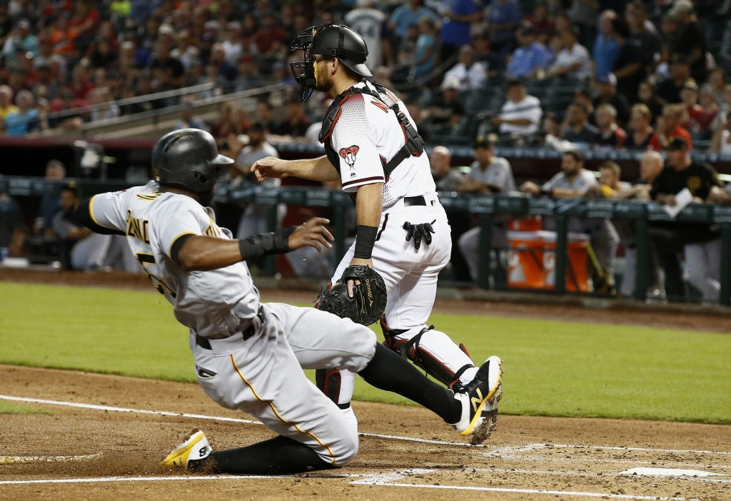 Pittsburgh Pirates' Gregory Polanco, left, scores a run as Arizona Diamondbacks catcher Jeff Mathis, right, waits for a late throw during the second i