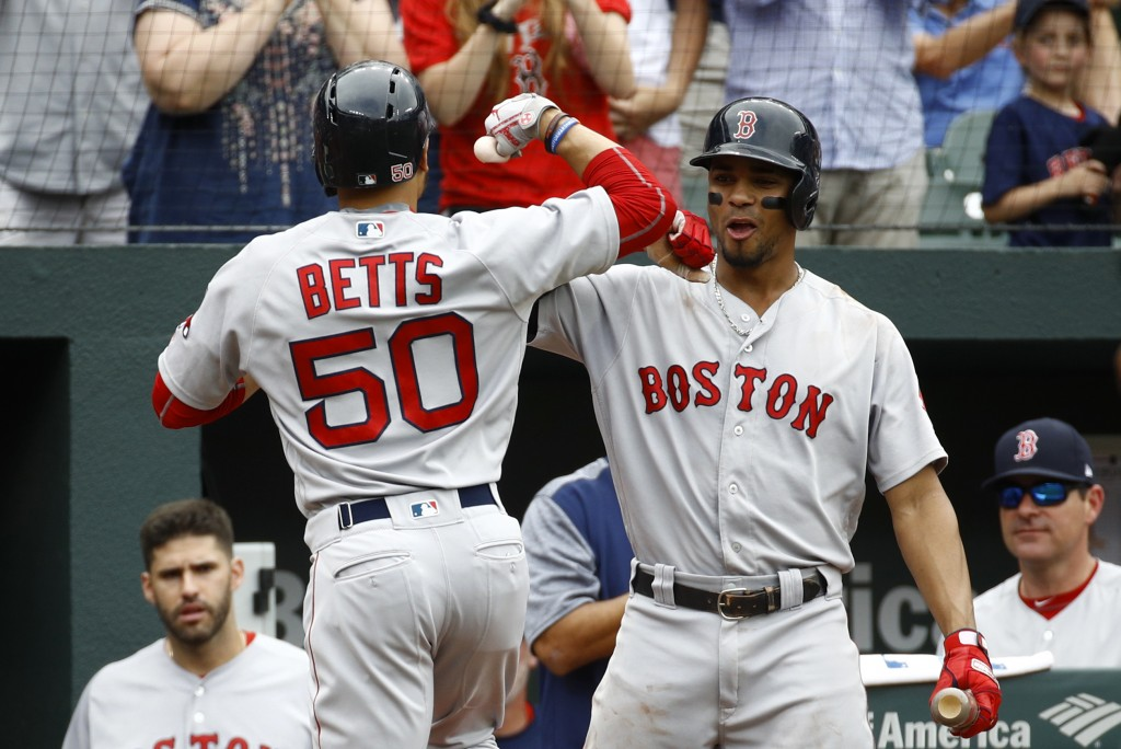 Boston Red Sox's Xander Bogaerts, right, greets teammate Mookie Betts after Betts rounded the bases on a solo home run in the third inning of a baseba