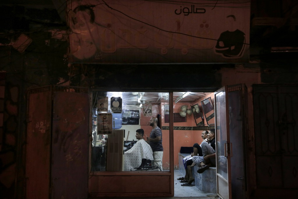 In this Feb. 16, 2018, photo, 18-year-old Abdullah gets his hair cut at a barbershop in Aden, Yemen. Even with a civil war in full swing, people seek