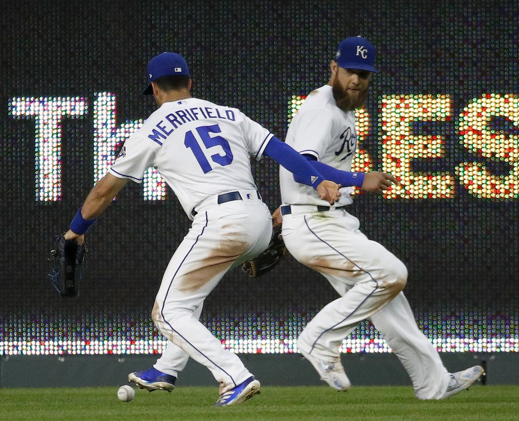 Kansas City Royals center fielder Whit Merrifield (15) and left fielder Alex Gordon chase a double hit by Cincinnati Reds' Jose Peraza during the seve
